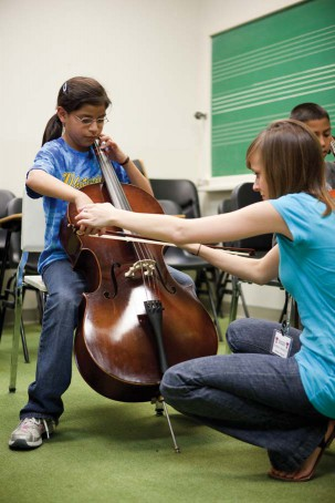 A Texas Tech University student demonstrates bowing technique to a Whiteside elementary student playing the cello