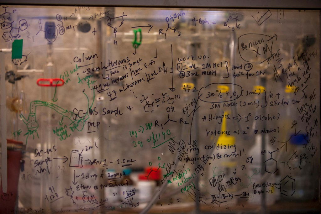 Chemical equations written on a transparent glass chalkboard