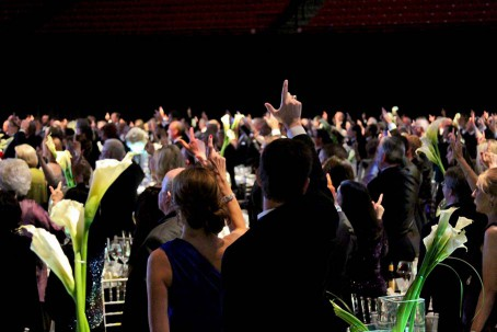 Guests raise their hands in the 'guns up' sign for the signing of the Matador Song