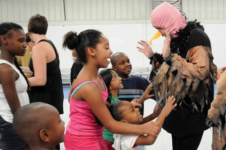 Theatre student in a bird costume interacting with children at the Guadalupe-Parkway Sommerville Centers