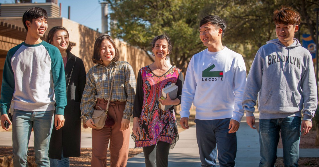 Susana Badiola walking with students on the Angelo State University campus