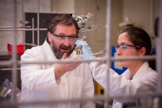 Michael Findlater marvels at a chemical mixture held by a student researcher